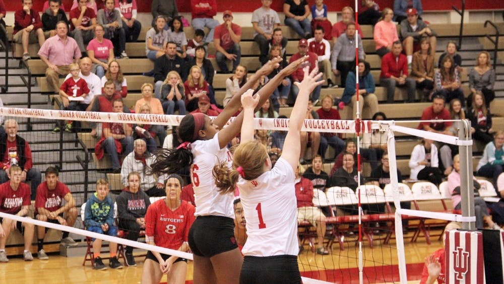 Deyshia Lofton (left) and Victoria Brisack from IU Hoosiers Volleyball defend the ball as they compete agaisnt Rutgers Scarlet Knights Friday night at the University Gym.