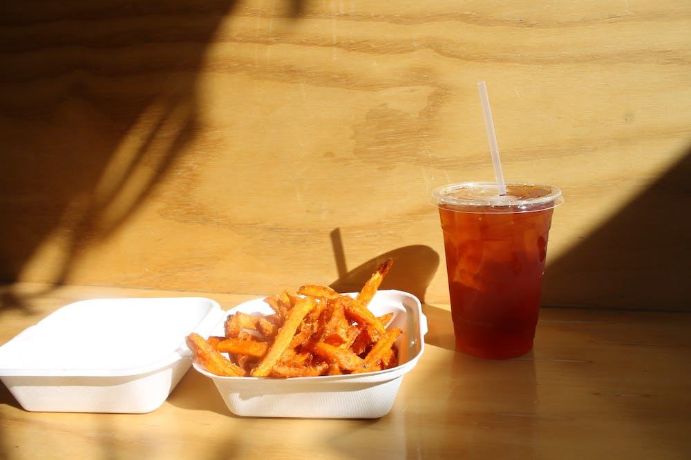 <p>A side order of sweet potato fries with an iced tea from the Owlery sits in the sun Monday. Sweet potato fries are one of the items you can get as part of the Owlery's Devour Bloomington take-out menu.</p>
