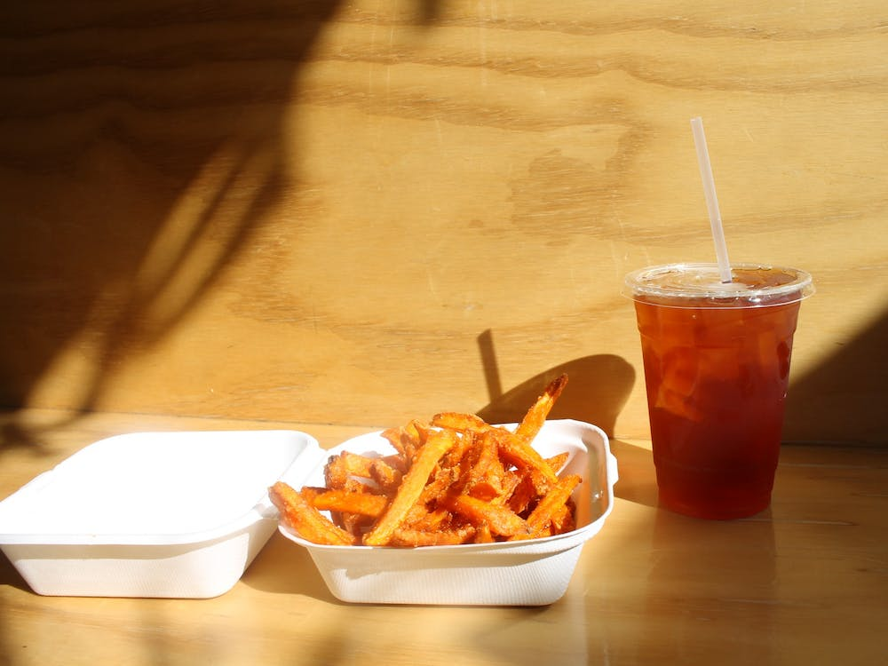 A side order of sweet potato fries with an iced tea from the Owlery sits in the sun Monday. Sweet potato fries are one of the items you can get as part of the Owlery's Devour Bloomington take-out menu.