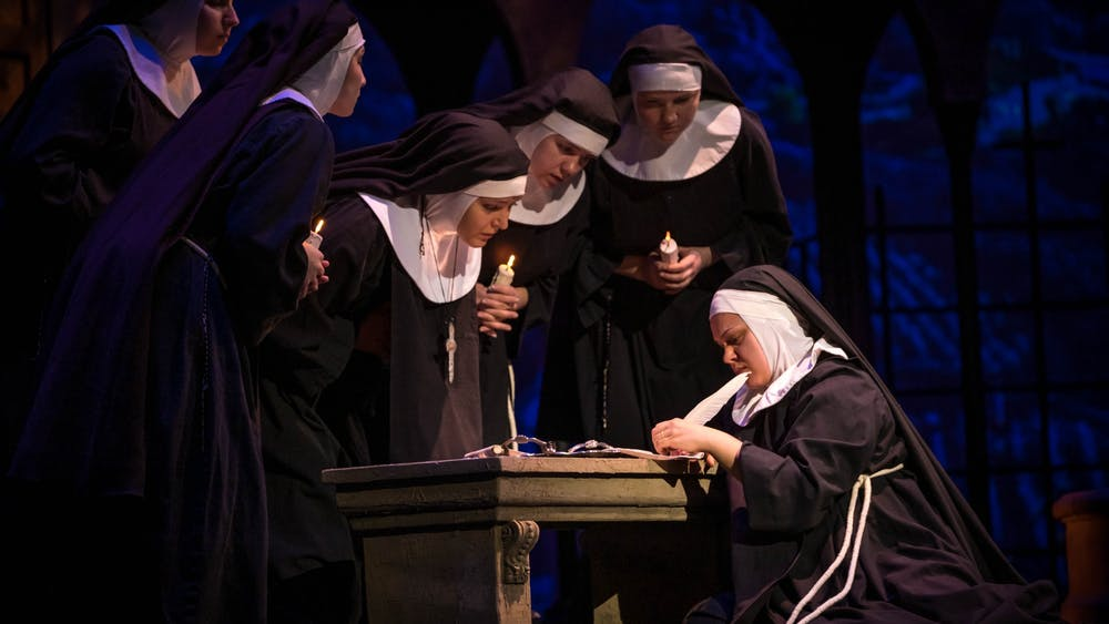 "Sister Angelica (Rose-Antoinette Bellino) signs away her claim to her inheritance during a dress rehearsal for ""Suor Angelica"" on Feb. 4 in the Musical Arts Center. IU Opera and Ballet Theater will perform ""Suor Angelica"" and ""Gianni Schicchi"" on Feb. 7-8 and Feb. 14-15 at the Musical Arts Center."