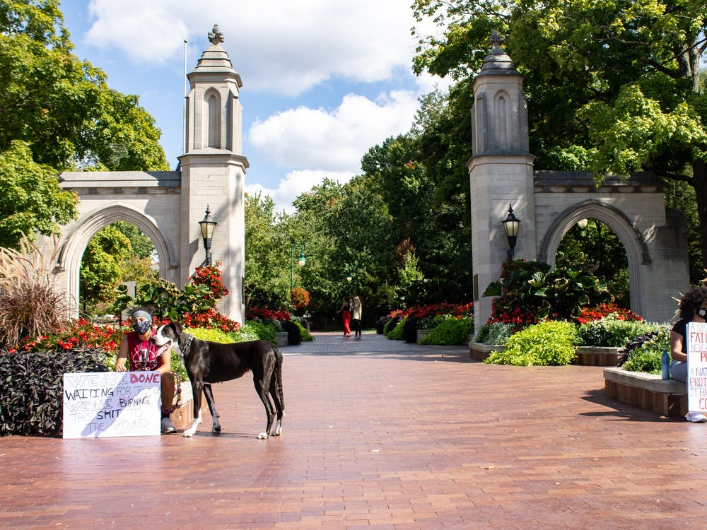Students hold signs protesting the Breonna Taylor case decision Sept. 24 in front of the Sample Gates.
