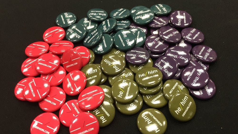 Buttons featuring different pronouns along with fill-in-the-blank pins are displayed at a 2019 GeekGirlCon event. The e-learning software Canvas now allows students to choose and display their preferred pronouns.