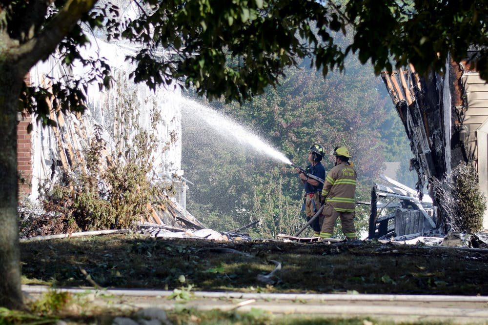 <p>Firefighters use firefighting foam on one of the houses damaged in the fire on S. Wickens St. last week. Residents first reported the fire the afternoon of Sept. 21. </p>