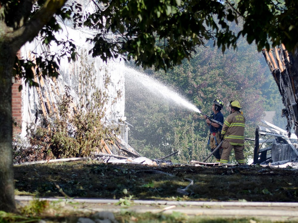 Firefighters use firefighting foam on one of the houses damaged in the fire on S. Wickens St. last week. Residents first reported the fire the afternoon of Sept. 21.