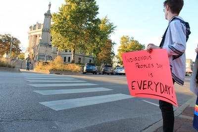 Caleb King holds an Indigenous Peoples' Day sign across the street from the Monroe County Courthouse on Monday. King later spoke to a crowd about the day in front of the courthouse.