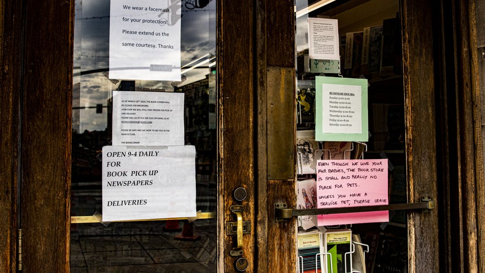 Signs on the front doors inform customers about visiting rules May 12 at the Book Corner. Some retail businesses and restaurants are preparing to reopen at 50% capacity Friday, while others are planning on remaining closed until they are able to reopen closer to full capacity.
