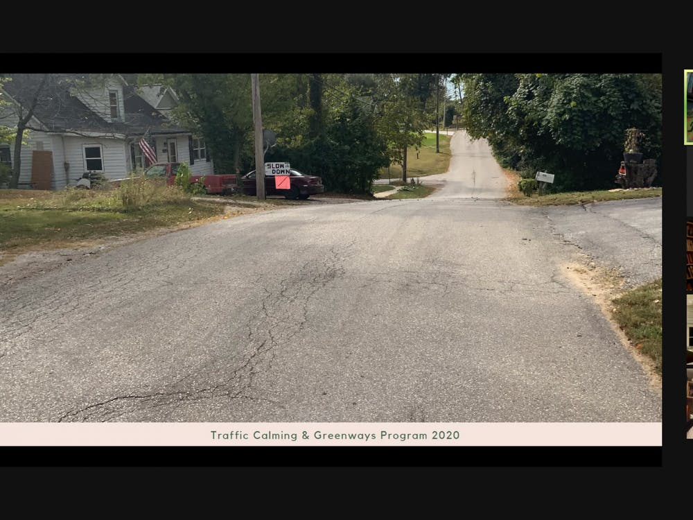 "Mallory Rickbeil, the city's bicycle and pedestrian coordinator, presents a photo of an ""incomplete street"" in Bloomington to the Bloomington City Council on Wednesday night. The council voted 9-0 to pass an ordinance that would establish a new process for residents and city officials to request traffic calming devices in parts of the city in an effort to decrease speeding."