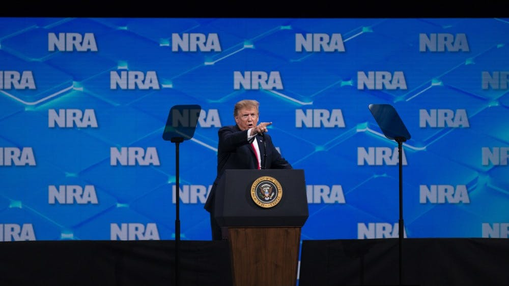 """President Trump points at the media and calls them """"fake news"""" during the NRA-ILA Leadership Forum on April 26 in Indianapolis. Trump spoke about the history of gun violence in America, and he introduced people who have experience dealing with intruders and shooters."""