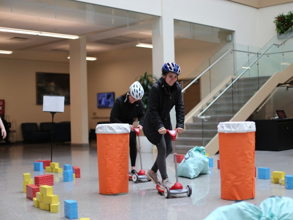 """Seniors Lexi Carmichael and Adriana Cogdill ride scooters through an obstacle course at """"Race for More than Four."""" This event was organized by Public Relations Student Society of America to raise awareness for childhood cancer treatment."""