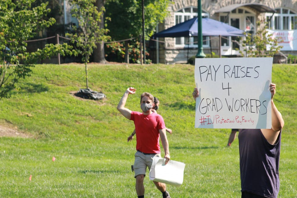 """<p>A protester holds a """"PAY RAISES 4 GRAD WORKERS"""" sign during a protest regarding inadequate pay Aug. 24, 2020, in Dunn Meadow. Each year, 8% of graduate workers&#x27; pay returns to IU.</p>"""