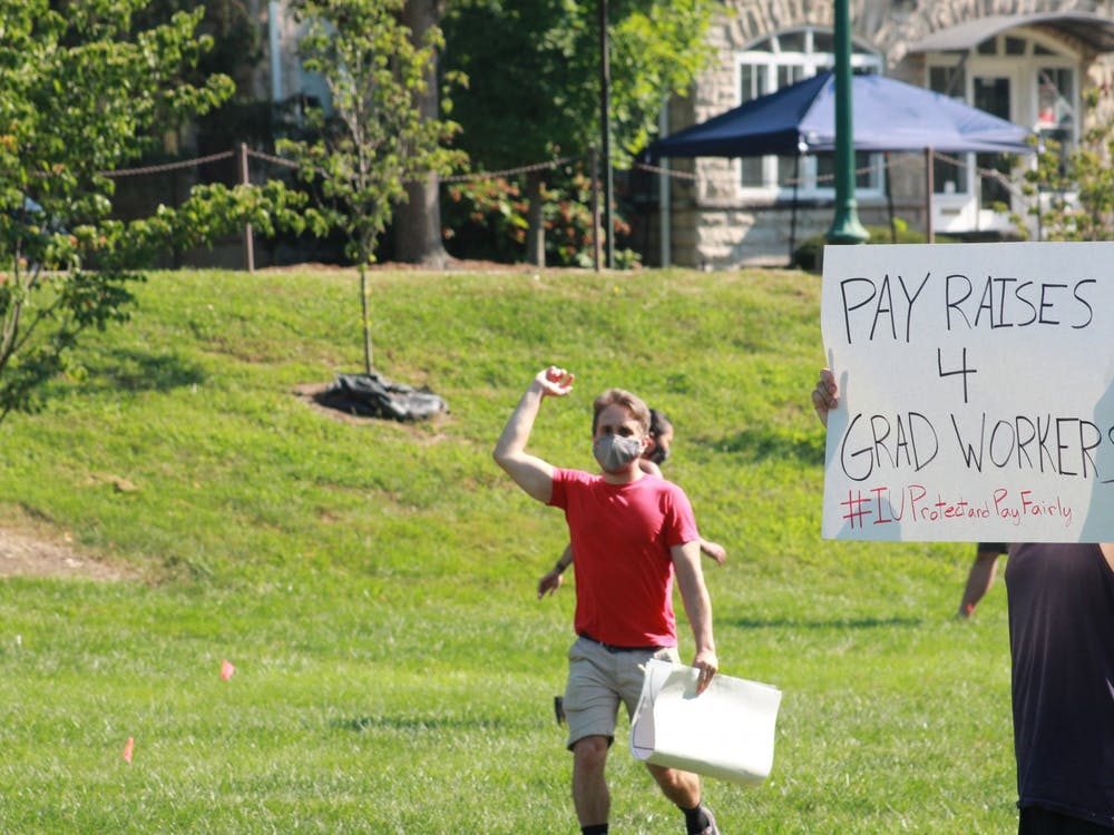 "A protester holds a ""PAY RAISES 4 GRAD WORKERS"" sign during a protest regarding inadequate pay Aug. 24, 2020, in Dunn Meadow. Each year, 8% of graduate workers' pay returns to IU."