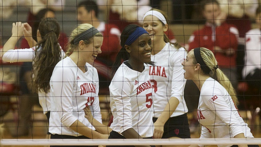 Members of the IU volleyball team celebrate after a point is scored during their game against Rutgers on Wednesday in University Gym.