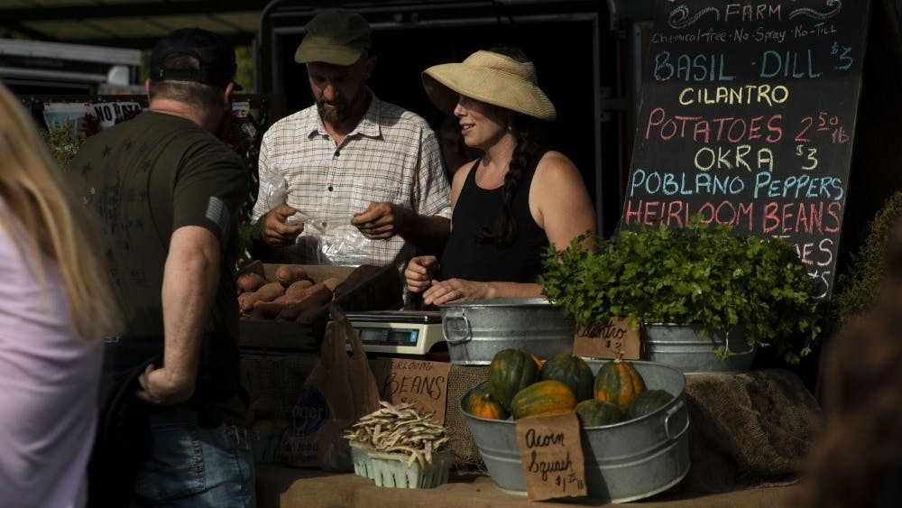 Sarah Dye and her husband Doug Mackey speak to a customer Sept. 28 at their booth for Schooner Creek Farm at the Bloomington Community Farmers' Market. They filed a lawsuit Friday against the city, mayor and park officials.