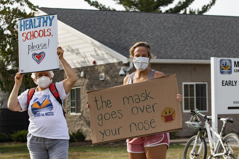 "<p>Bloomington educators Glee Noble and Jenny Noble-Kuchera stand together during the &quot;Teachers vs. COVID&quot; rally Sept. 21. at the Education Resource Center for the Monroe Country Community School Corporation. ""The mask goes over your nose,"" reads Noble-Kuchera's sign.</p>"