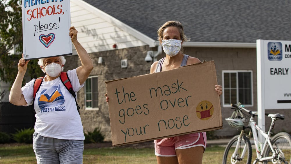 """Bloomington educators Glee Noble and Jenny Noble-Kuchera stand together during the """"Teachers vs. COVID"""" rally Sept. 21. at the Education Resource Center for the Monroe Country Community School Corporation. """"The mask goes over your nose,"""" reads Noble-Kuchera's sign."""
