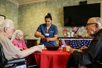 Gabby Carrillo assists several patients at the Californian-Pasadena nursing home July 3, 2018, in Pasadena, California.