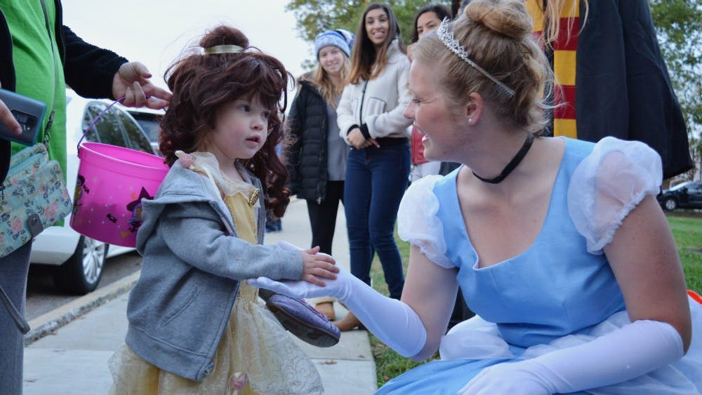 """Senior Regan Gibson of Theta Phi Alpha, dressed as Cinderella, greets 4-year-old Savannah Altop, dressed as Belle, during Safe Halloween Wednesday afternoon on the Jordan Avenue extension. Kiera Knightley once told Ellen DeGeneres that she deems movies like """"Cinderella"""" and """"Ariel"""" as anti-feminist, and she doesn't allow her kid to watch them."""