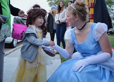 "Senior Regan Gibson of Theta Phi Alpha, dressed as Cinderella, greets 4-year-old Savannah Altop, dressed as Belle, during Safe Halloween Wednesday afternoon on the Jordan Avenue extension. Kiera Knightley once told Ellen DeGeneres that she deems movies like ""Cinderella"" and ""Ariel"" as anti-feminist, and she doesn't allow her kid to watch them."