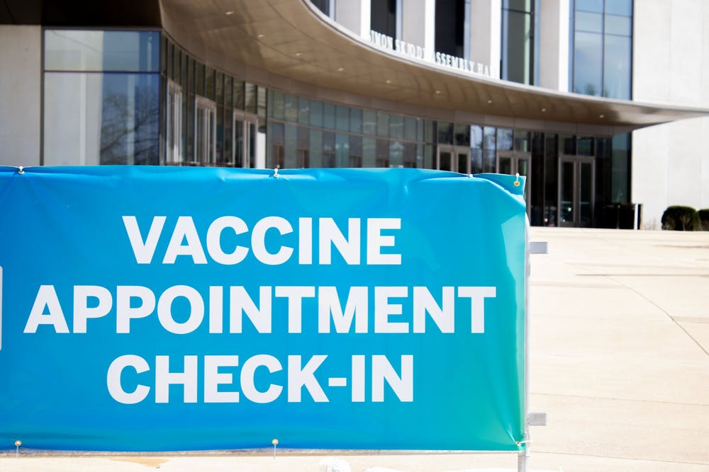 <p>A sign appears Tuesday directing visitors towards the vaccine clinic inside Simon Skjodt Assembly Hall. All Indiana residents over age 16 can begin scheduling their COVID-19 vaccine starting Wednesday.</p>