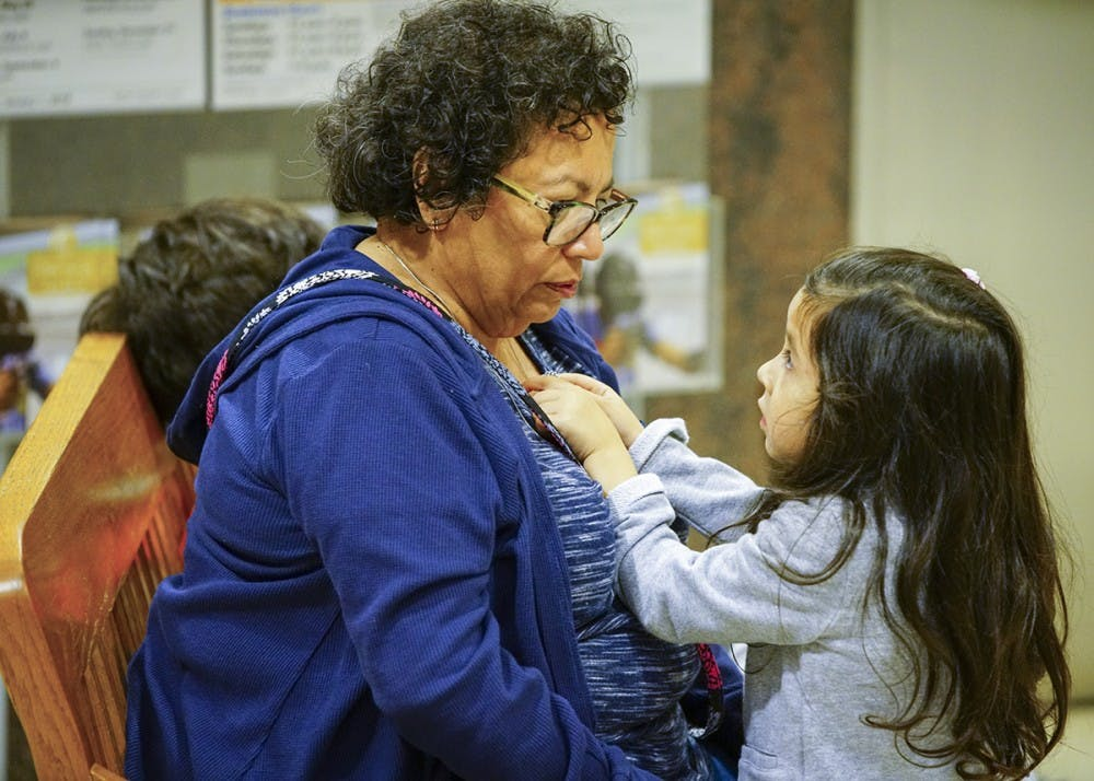 <p>Elosia plays with her grandmother Rochelle Martin's necklace during the Hispanic Heritage Day Celebration on Sunday afternoon in the Monroe County Public Library.&nbsp;</p>