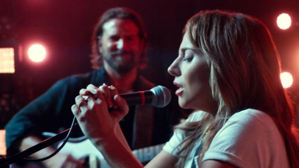 """A Star is Born"" is set to release Oct. 5. Lady Gaga's character, Ally, takes the mic onstage as Bradley Cooper looks on."