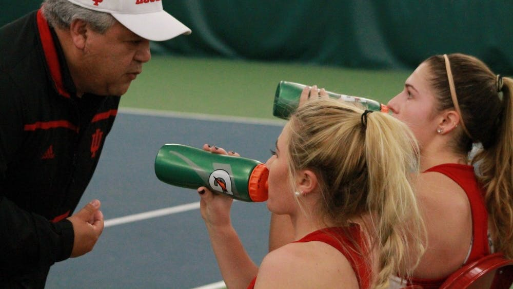 Head coach Ramiro Azcui talks with then-sophomores, now juniors, Madison Appel and Natalie Whalen in February at a match against DePaul. This will be Azcui's second season as head coach.