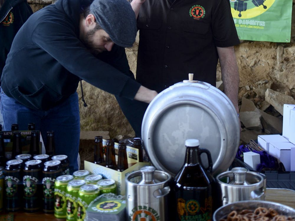 Phill Green takes a sip of the Imperial Pilsner while setting up the People's Brewing Company's booth at the 5th Annual Bloomington Craft Beer Festival on Apr. 11, 2015.