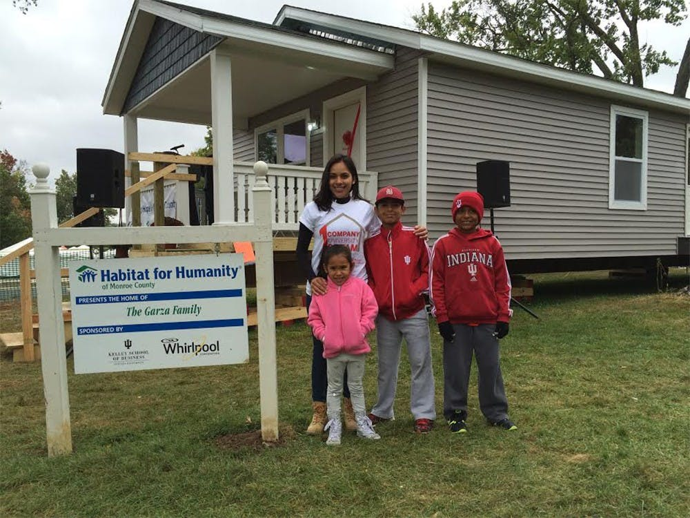 Nereyda Garza poses in front of her newly-completed home with her children Jonathan, Axel and Julianna. The home was completed Saturday morning and moved to W 12th Street on Sunday.
