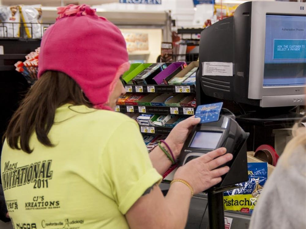 Cassie Winders, 33-year-old single mother of four, uses her EBT card to purchase food for dinner Nov. 18, 2013, at Kroger. Indiana is adding two new benefits to the Supplemental Nutrition Assistance Program, commonly known as food stamps.