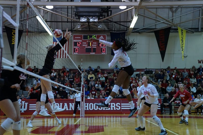 Junior middle blocker Deyshia Lofton spikes the ball against two Nebraska defenders Nov. 17 in University Gym. Lofton finished the season with 281 kills and was named to the All-Big Ten Second Team.