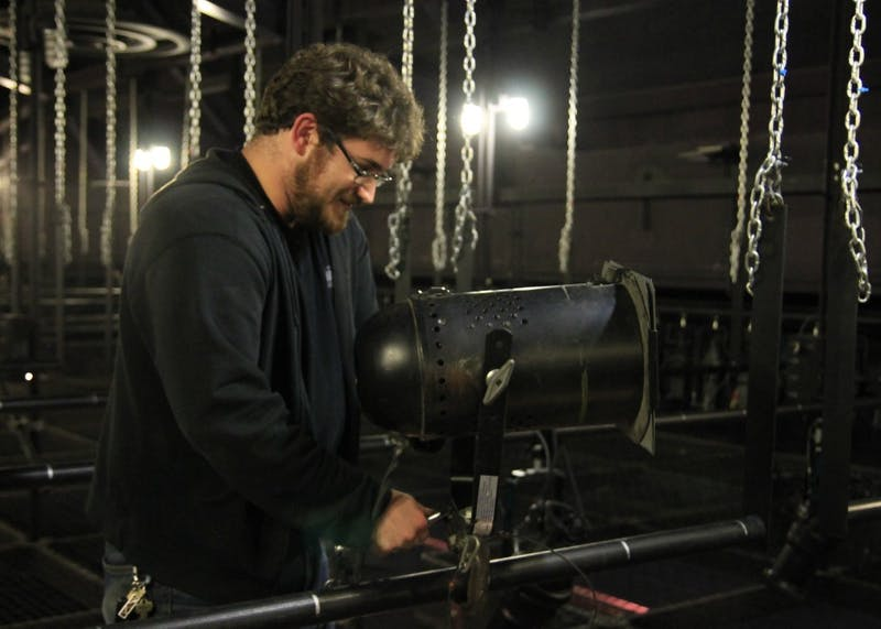 """Lighting designer Anthony Stoeri hangs lights above the Wells-Metz Theater along with his crew. Stoeri will be the master electrician and lighting designer for the upcoming show, """"Peter and the Star Catcher."""""""