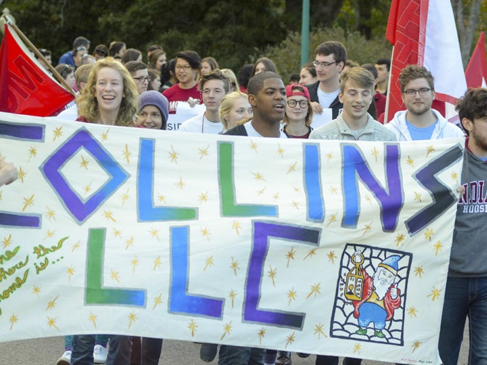 Collins Living Learning Center President Stephon Glider leads the way as residents from various dorms show their cream and crimson pride during the homecoming parade Friday evening on Woodlawn Avenue. The parade is hosted every year during homecoming weekend to hype up Hoosiers before the big football game.