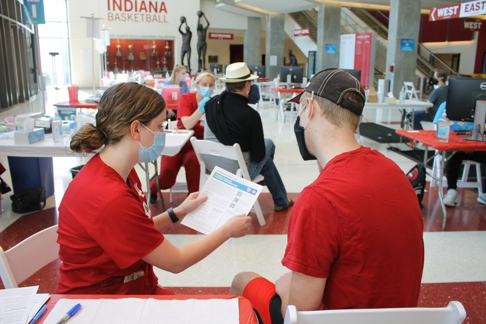 <p>Junior Bryce Asher talks with nursing student Maddy Anderson before receiving the COVID-19 vaccine April 12 at Simon Skojdt Assembly Hall. IU announced Friday that the COVID-19 vaccine will be required for all students, staff and faculty beginning in the fall.</p>