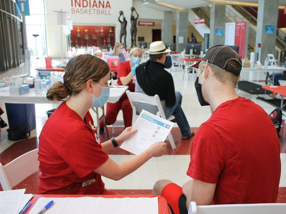 Junior Bryce Asher talks with nursing student Maddy Anderson before receiving the COVID-19 vaccine April 12 at Simon Skojdt Assembly Hall. IU announced Friday that the COVID-19 vaccine will be required for all students, staff and faculty beginning in the fall.