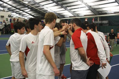 IU's men's tennis team gathers in a circle with coaches before a men's singles match against Purdue at the IU Tennis Center in 2017.