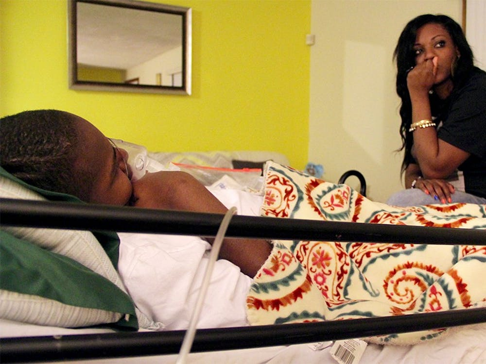 DeAndra Yates sits on her son's hospital bed on Mar. 5 at their home in Indianapolis. Her son, Dre Knox, was shot in the head in 2014 when he was 13 years old. Since then, he hasn't been able to walk ot talk. Over the past two years, DeAndra has become a vocal advocate against gun violence.