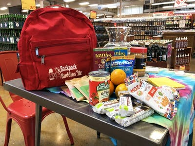 A Backpack Buddies backpack and food sit on a table Aug. 20 in Lucky's Market. Children enrolled in the Backpack Buddies program are given enough food to make five meals.