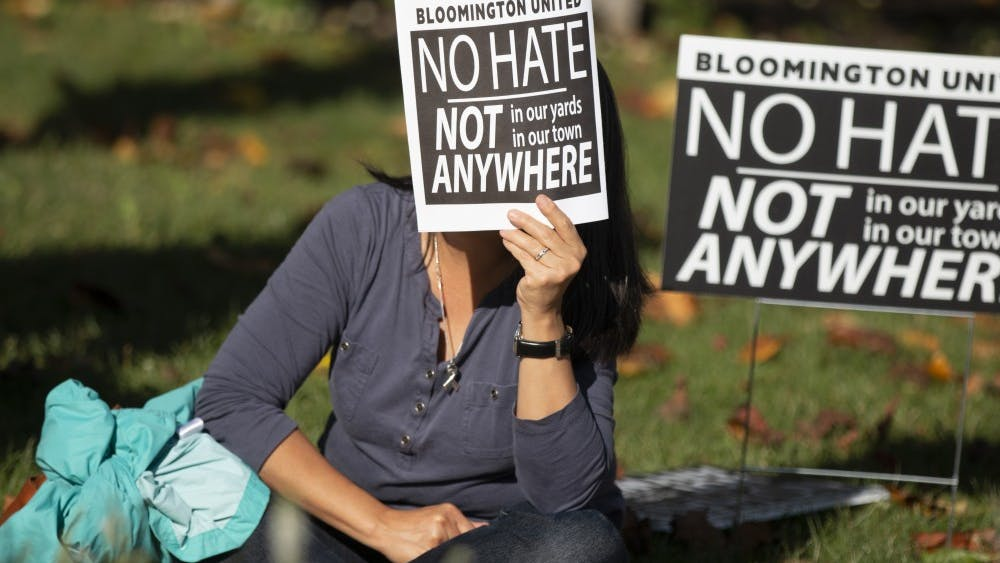 A woman covers her face from the sun with a Bloomington United program Aug. 27, during a solidarity event at the Monroe County Courthouse. The event featured several speakers who talked about their experience with racism and hate and how to overcome it.