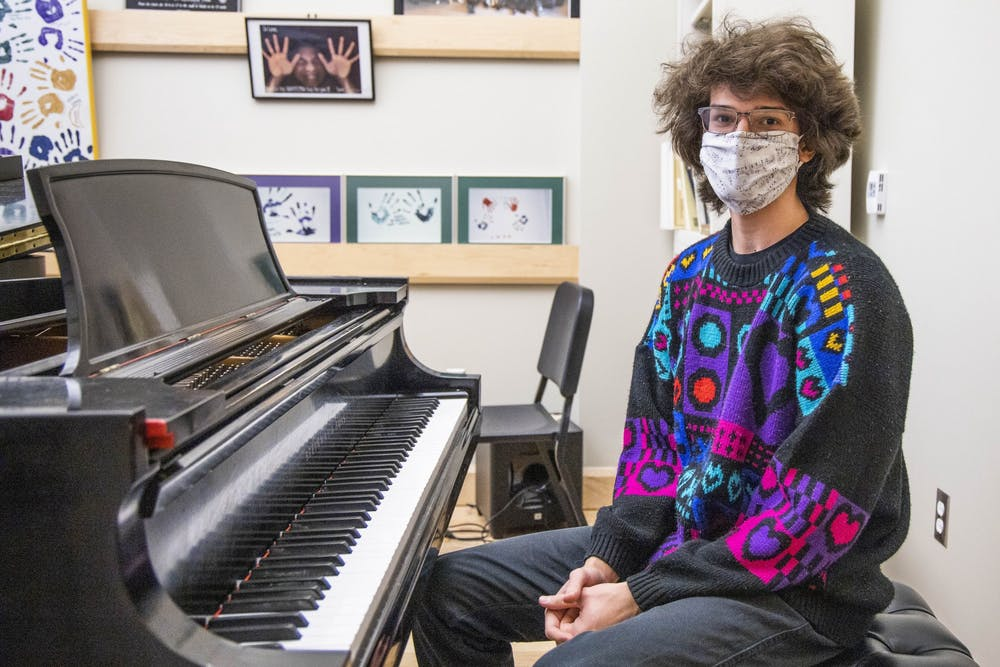 <p>Erik Wakar sits next to a piano March 2 in the Jacobs School of Music East Studio Building. Waker began taking piano lessons with her older brother at age six.</p>