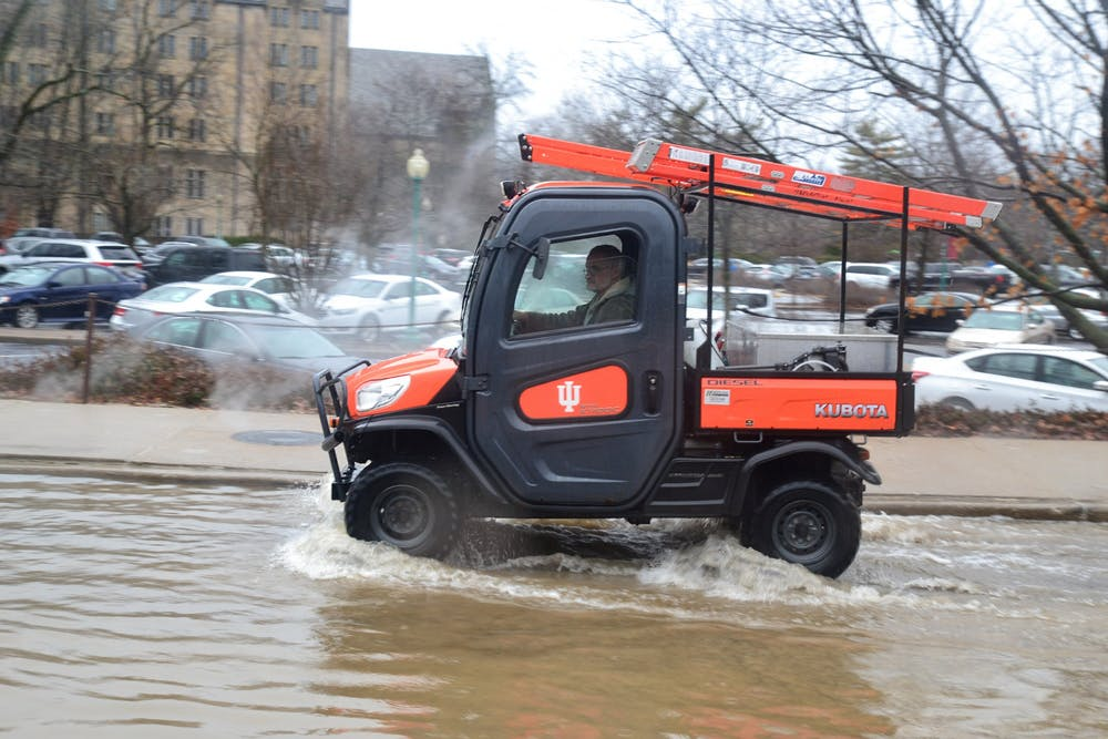 <p>A man drives an IU-branded utility vehicle Feb. 7, 2019, through a flooded Forest Avenue. With warmer temperatures projected, it is likely that Bloomington could experience flooding due to melting snow this week. </p>