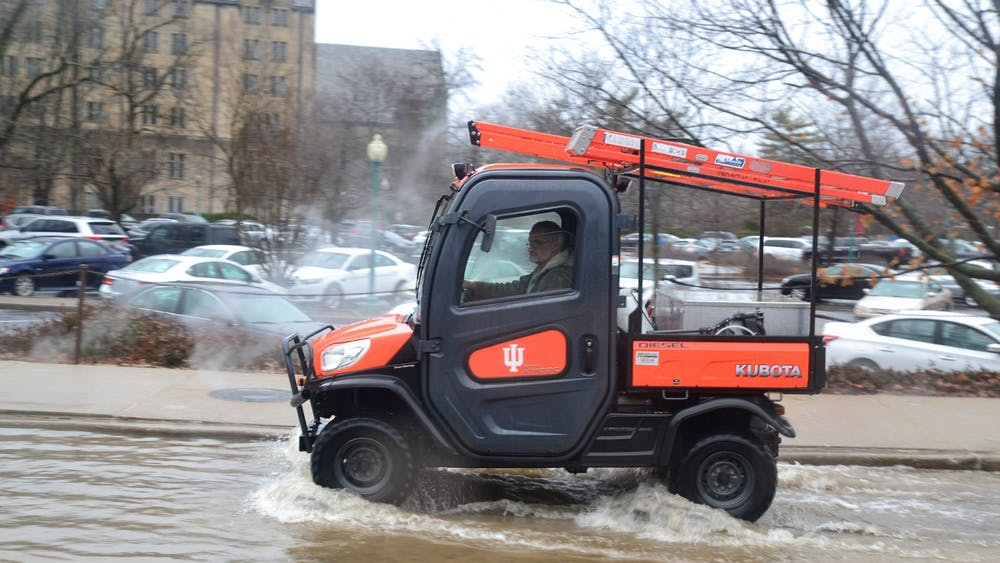 A man drives an IU-branded utility vehicle Feb. 7, 2019, through a flooded Forest Avenue. With warmer temperatures projected, it is likely that Bloomington could experience flooding due to melting snow this week.
