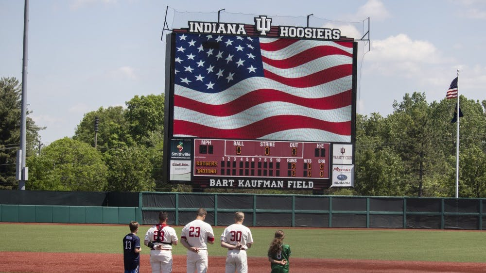Senior catcher Ryan Fineman, junior left-handed pitcher Andrew Saalfrank and junior infielder Scotty Bradley stand with two children on the pitching mound May 18 at Bart Kaufman Field. Players stood for the national anthem before playing Rutgers.