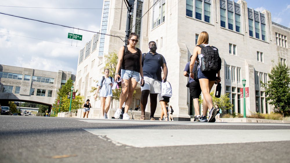 Students cross the street at the corner of North Fee Lane and East 10th Street. Many are returning to in-person classes during the fall semester.