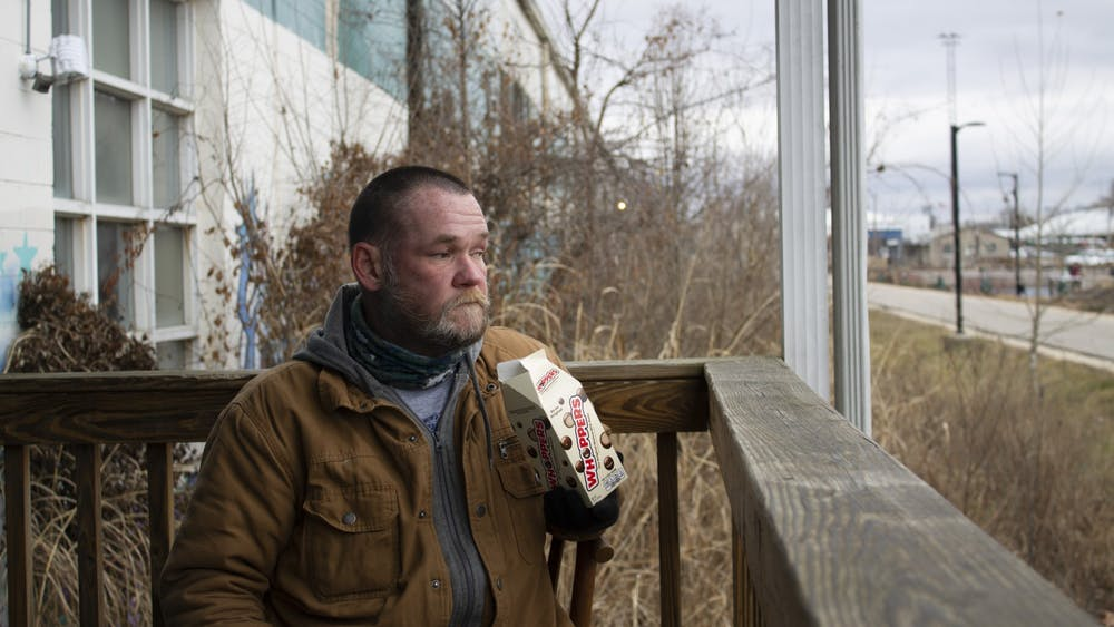 "Bloomington resident Jason ""Bubba"" Oliphant, 47, sits outside the new Beacon winter shelter near Switchyard Park on Jan. 26. Oliphant has been living at the shelter next door, A Friend's Place, which is also run by Beacon."