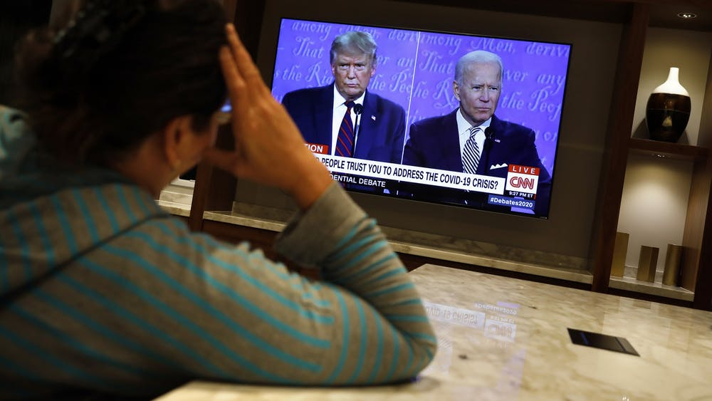 A woman watches a TV as President Donald Trump and Democratic presidential nominee Joe Biden participate in the first presidential debate at the Health Education Campus of Case Western Reserve Universit Sept. 29in Cleveland, Ohio.