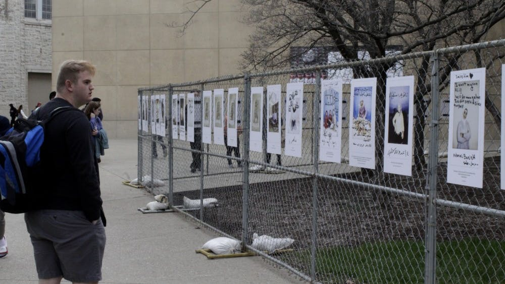 Kade Padgett, Late Nite director at the Indiana Memorial Union Board, looks at refugee posters.