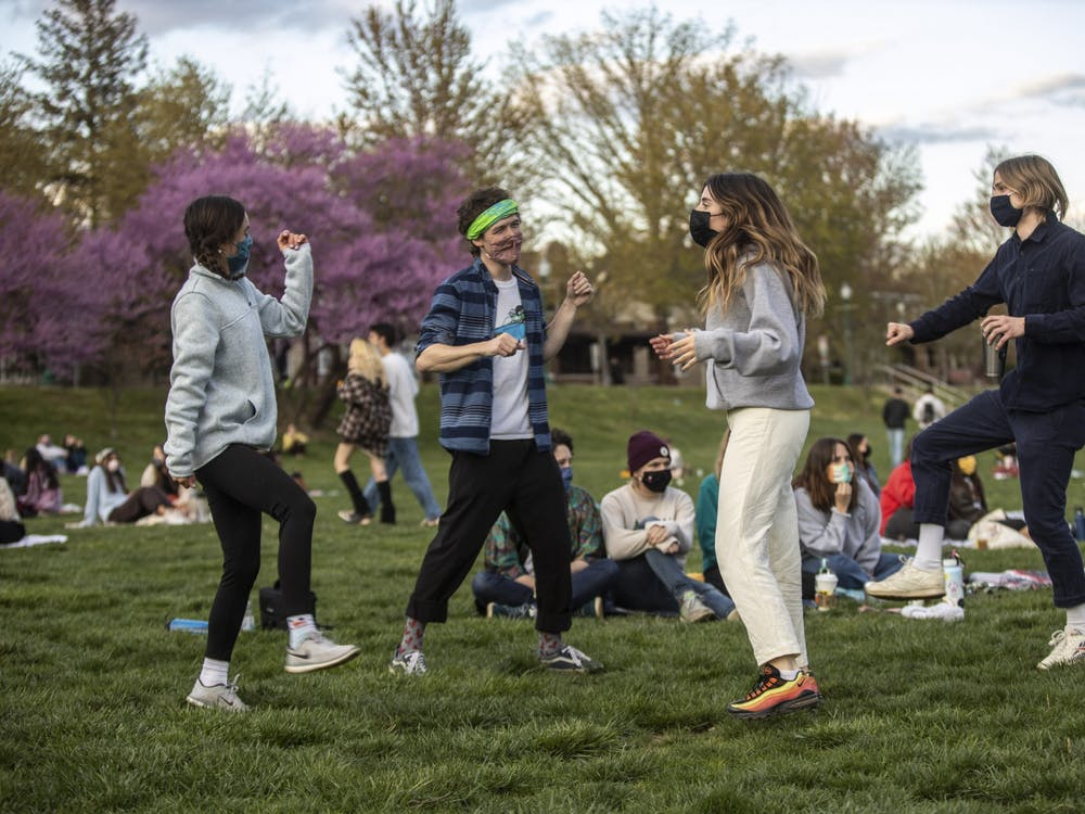 """Then-juniors Sydney Johnson and Emery Hightower, then-sophomore Ollie Grcich and then-senior Sam Boland, co-president of Bloomington Delta Music Club, dance during the BDMC Presents concert April 15, 2021, in Dunn Meadow. The first """"Swing in September"""" concert will take place Sept. 3, 2021, in Dunn Meadow."""