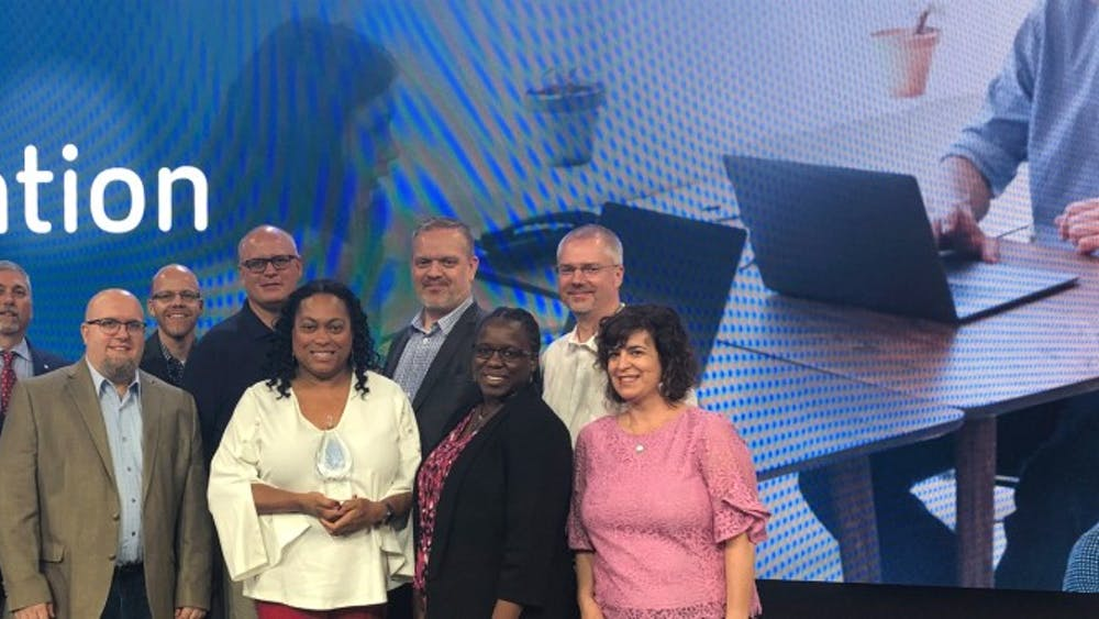 Stephanie Cox holds the Citrix Innovation Award with her IU team on the Citrix Synergy stage in Atlanta. IU won the award for AT Desktop, a software service accessible to people with visual impairments.