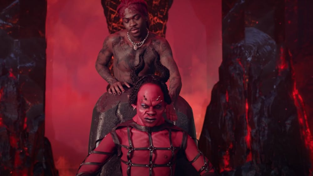 "Lil Nas X dances behind a portrayal of the devil in a screenshot from the music video for his song ""MONTERO (Call Me By Your Name)."" The video sparked an internet controversy after its release March 26 due to its sexual and demonic themes."