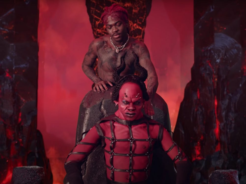 """Lil Nas X dances behind a portrayal of the devil in a screenshot from the music video for his song """"MONTERO (Call Me By Your Name)."""" The video sparked an internet controversy after its release March 26 due to its sexual and demonic themes."""